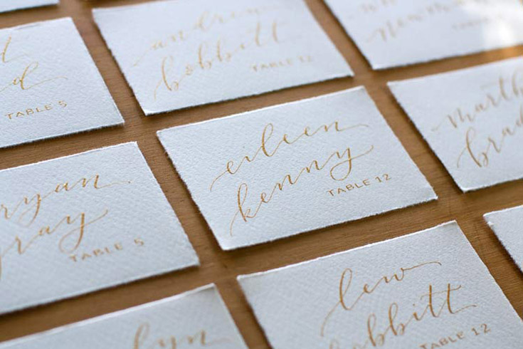 Gold calligraphy escort cards by Taryn Eklund Ink